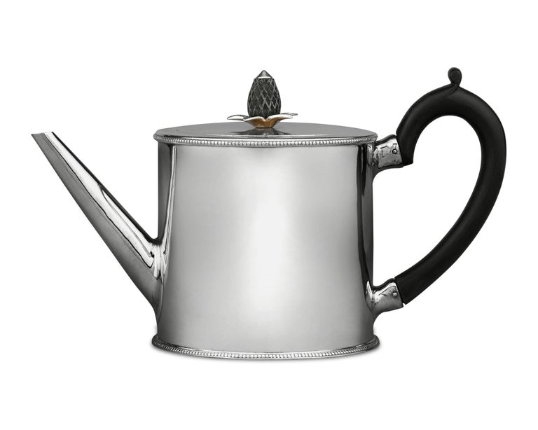 A work of refinement, this George III silver teapot was crafted by the legendary female silversmith Hester Bateman. Its round form is accentuated by Bateman's signature beaded trim, while a pineapple finial and handle, both carved from ebony, add