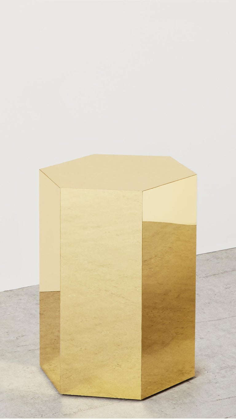 """Askew side table, Arielle Lichten  A brass finish side table in a hexagonal shape.  Measures: 12"""" W x 12"""" L x 16"""" H  Material: Brass  Custom Sizes and finishes available  Arielle Lichtens work is rooted in a fascination with materials and"""