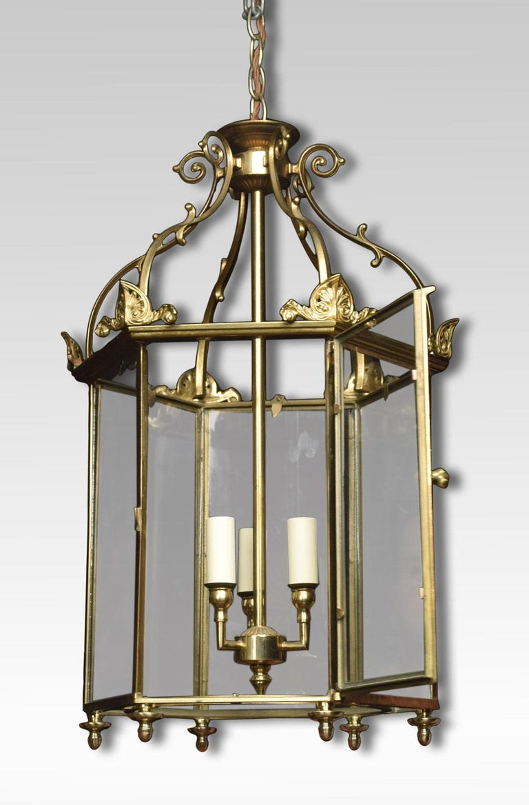 Hexagonal brass hall lantern of George III style with six scrolled ribs and glazed panels enclosing three lights. The lantern has been rewired.