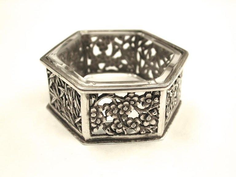 Hexagonal Chinese silver salt cellar, Cumwo, Hong Kong, circa 1890. Depicting bamboo, Prunus blossom and Chinese Iris. Heavy quality with original clear glass liner.