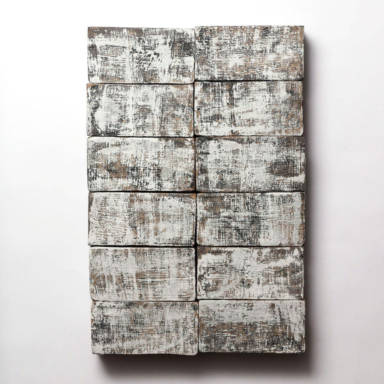 Based on the I Ching, an ancient Chinese divination text, this one-of-kind ceramic wall sculpture is composed of handmade stoneware blocks. Each block has a complex layered black and white finish, with a texture reminiscent of wood or stone, and is