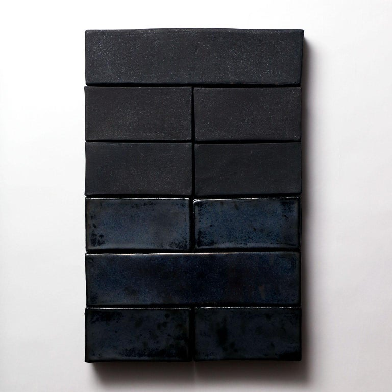 Based on the I Ching, an ancient Chinese divination text, this one-of-kind ceramic wall sculpture is composed of handmade stoneware blocks. Each block is individually finished with either a metallic black matte finish or a glossy iridescent black