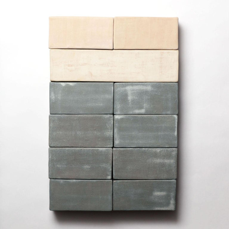 Based on the I Ching, an ancient Chinese divination text, this one-of-kind ceramic wall sculpture is composed of handmade porcelain blocks. Each block is individually glazed with textural matte glazes in pink, cream, and blue tones, then fastened