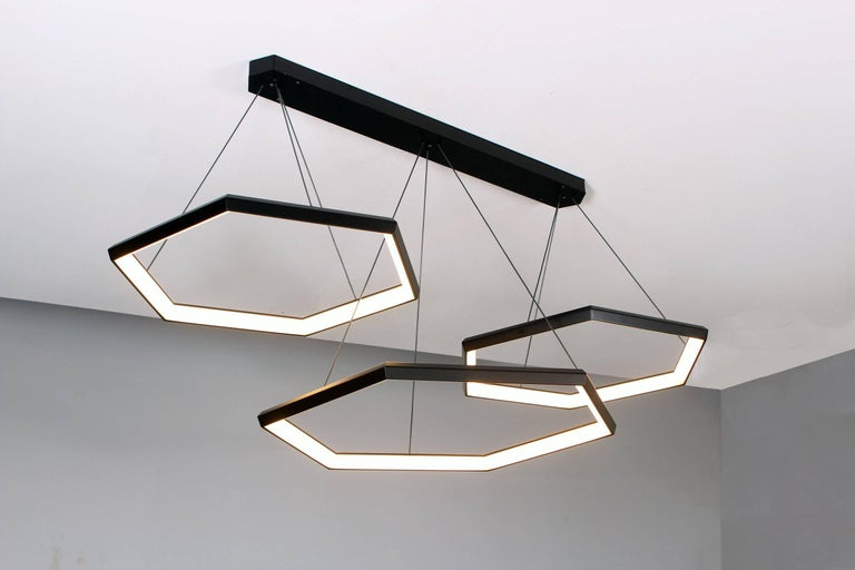 HEXIA TRIO HXT34 is a linear arrangement using three of our HEXIA fixtures. Three rings are suspended from a linear canopy. This fixture can be customized to utilize different sizes. Multiple fixtures can be added to create a layered