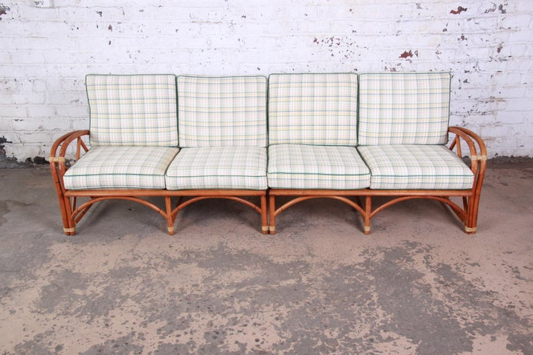 A nice and unique Mid-Century Modern Hollywood Regency style sofa from the Ashcraft line by Heywood-Wakefield. The sofa features a gorgeous bent rattan frame, and the original plaid upholstery in green, pink, yellow, and white. The frame has clean