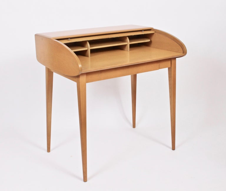 Classic American Mid Century Heywood-Wakefield Petite Birch Roll Top Desk. With finished back.  Featuring six interior compartments.  Legs attach and detach with wingnuts. Amber finish. Rarity. Sleek. Storage. Small footprint. Eagle burn stamp