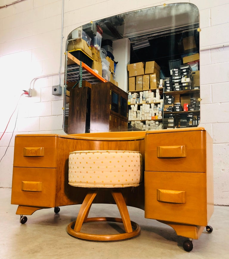 """Vintage 1950s Heywood Wakefield maple wood vanity with mirror and foot stool set in the champagne finish. The vanity has 4 drawers for storage and comes with matching foot stool. Mirror is in excellent condition. Stool measures 18"""" diameter x 19"""""""