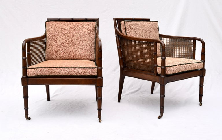 A pair of caned, faux bamboo Mahogany club, lounge or occasional chairs on brass casters. Beautifully maintained, the pair has been fully detailed and reupholstered. Caning is immaculate. Removable upholstered and fitted insert decks for support