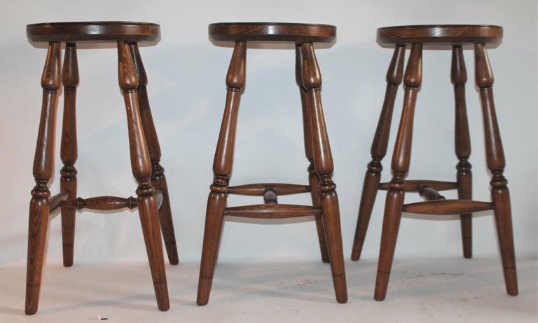 Set of three Old Hickory Furniture Company bar stools in dark wood finish. Fantastic plank seats.