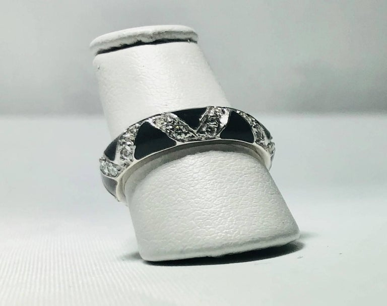 Hidalgo 18 Karat White Gold Diamonds and black enamel stackable band ring. This Hidalgo classic creation is created in 18 white gold and weighs 4.9 grams and 3.2dwt.. There are 24 full cut round diamonds .48 carats total weight, average color-G-H