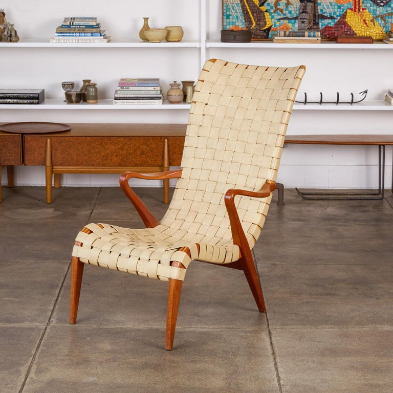 A Pioneer of Swedish Modern, a uniquely functionalist discipline of Scandinavian design, Axel Larsson designed modest living pieces with an eye for blonde or bentwood, and woven surfaces. This high-backed lounge chair, an obvious precursor to the