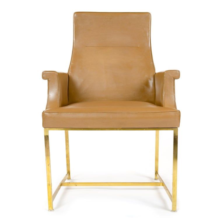 A high back armchair with the original tan leather upholstery and a solid brass base.