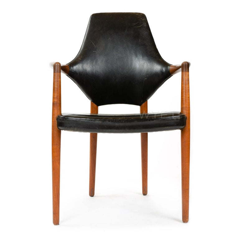 A Scandinavian Modern armchair designed by Helge Vestergaard Jensen. This high back chair features a dynamically shaped back, solid teak wood frame, and is upholstered with black leather. Chair is in original condition with lovely patinated leather.