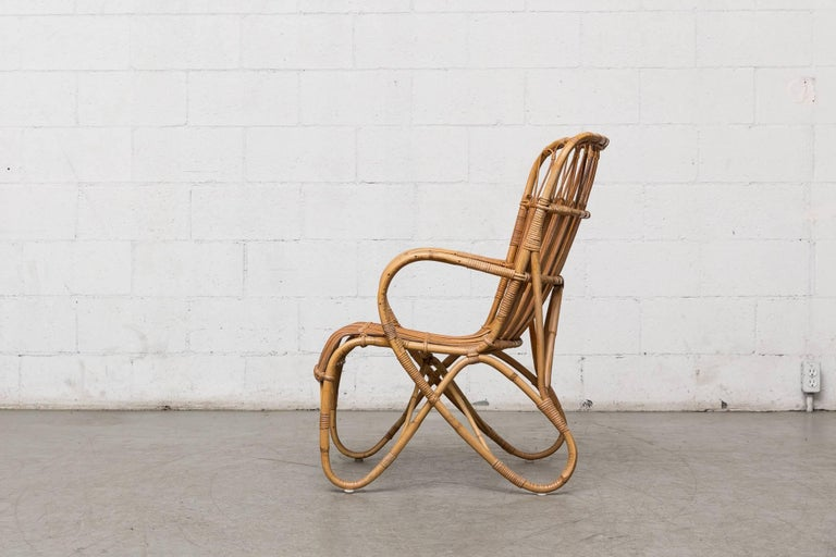 Midcentury tall back bamboo lounge chairs by Rohe Noorwoldswith beautiful golden patina and more intricate weaving detail than most. Four strands of bamboo. Good original condition with some wear consistent with its age and use.