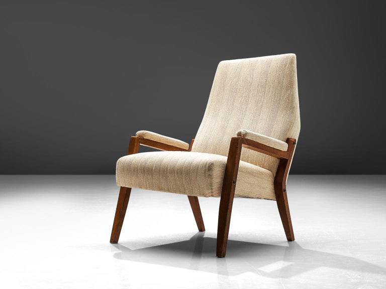 Italian lounge chair, beige fabric, stained beech, Italy, circa 1950.  This elegant armchairs in wood and beige fabric upholstery. The high tapered wooden legs provide an open look to the L-shaped seating. Beautiful detail is the kinked rear leg.