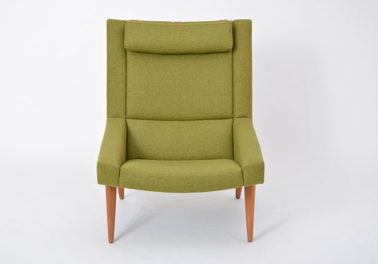 This lounge chair was designed by Illum Wikkelsø in the 1960s and produced by Soren Willadsen, Denmark. The cone shaped legs are made from solid teak. It has been reupholstered in a green wool.