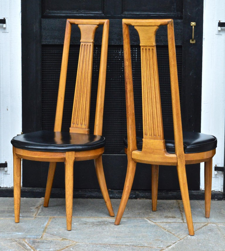 A sexy and sophisticated pair of midcentury side chairs of ash by esteemed maker Tomlinson. Ample rounded seats of original black leatherette combined with the dramatic high back of this chair makes it particularly stylish.