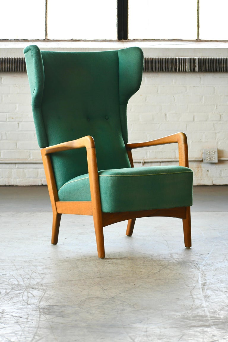 Classic Fritz Hansen high back lounge chair with open armrests designed by Soren Hansen and manufactured in the 1940s by Fritz Hansen. One of Fritz Hansen's most enduring designs elegant and comfortable. Nicely grained elm frame later upholstered in