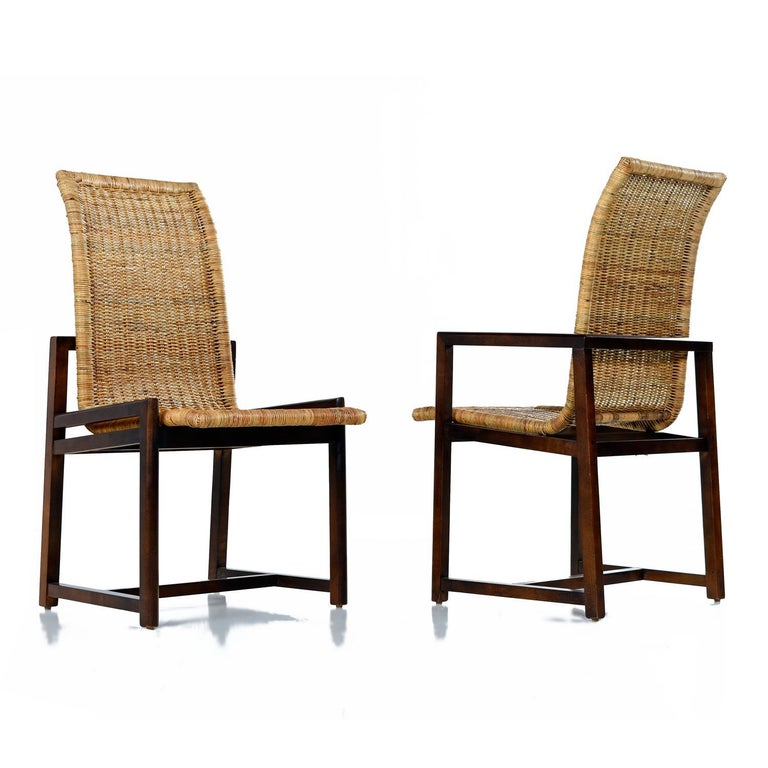 Curvaceous high back bucket seats comprised entirely of woven rattan. The dark toned beechwood frames are a handsome compliment to the woven cane. Although only subtly different, there are two armchairs in this set of six. Made by Century Furniture