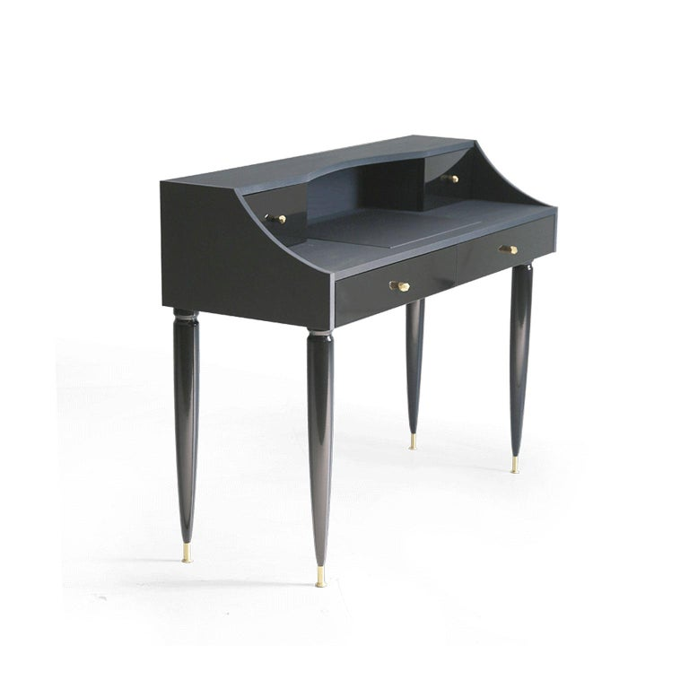 Refined elegance and classic design characterize the Kanttari Writing Desk. The definition of rich furniture design, this beautiful writing desk is handmade with soft to touch black panels and leather top. Luxurious brass accents on handles and legs