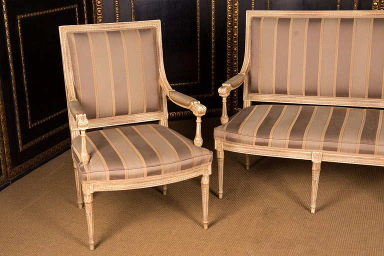 Solid beechwood, carved. Straight backrest frame. Frame with relief carved frame on tapered legs. Easily rearward, richly carved armrests. The seat and backrest are finished with a Classic upholstery. The set is in a used condition.