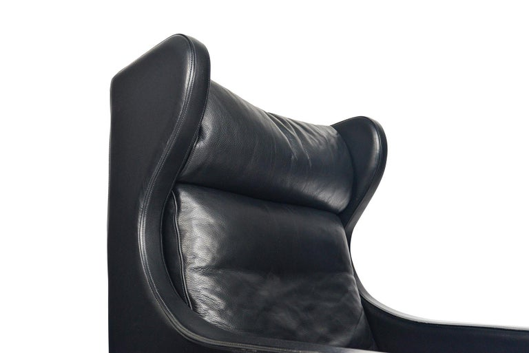 This stately highback leather lounge chairs was crafted by Skipper Møbler. The wingback design holds three cushions upholstered in original pebbled black leather. The chair stands on a routed cherrywood base. In excellent original condition.