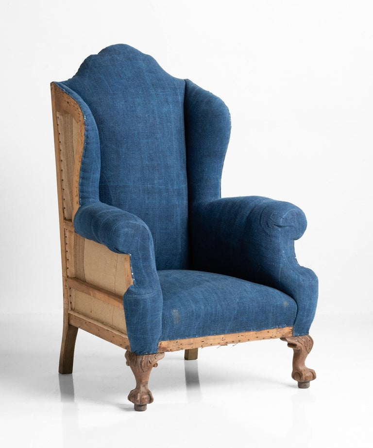 Highback Winged Armchair, England, circa 1910  Partially upholstered in beautifully patinated indigo dyed fabric with exposed back and sides as well as front ball and claw feet.