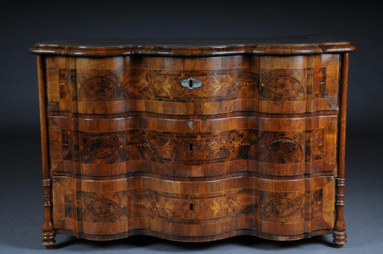 Highly interesting inlaid Baroque commode, circa 1740  Various fine wood veneers on solid fir wood. Profile framed, reasonably curved frame on pressed ball feet. Just 3 Schübiger, strongly curved in the front body. Sides and cover plate with