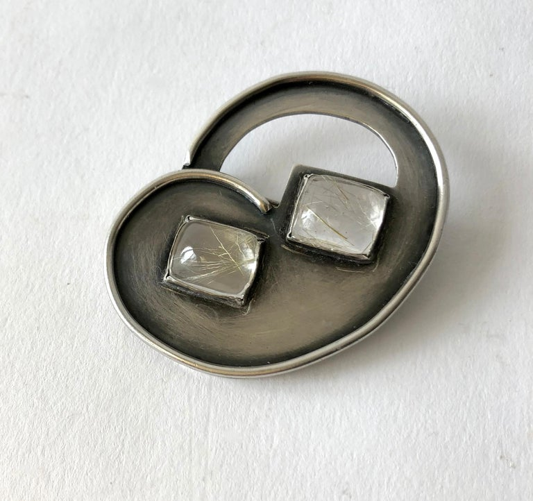 Modernist sterling silver and rutilated quartz brooch created by enamelist and jeweler, Hilda Kraus.  Brooch measures 1 3/4