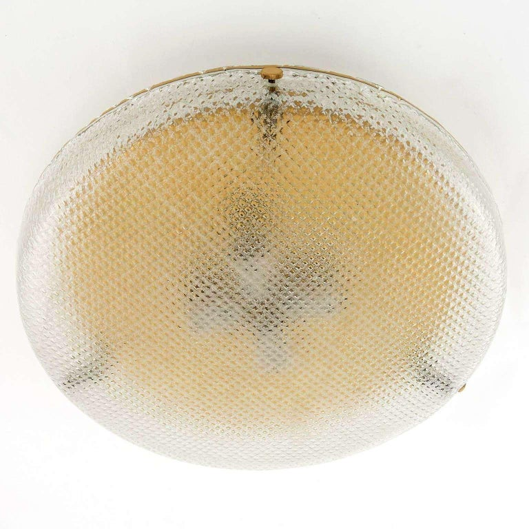 A wonderful light fixture by Hillebrand, Germany, manufactured in midcentury, circa 1970 (late 1960s or early 1970s).  It can be used as wall or ceiling lamp. A round textured glass with a grid pattern is mounted with three brass bolts on a polished