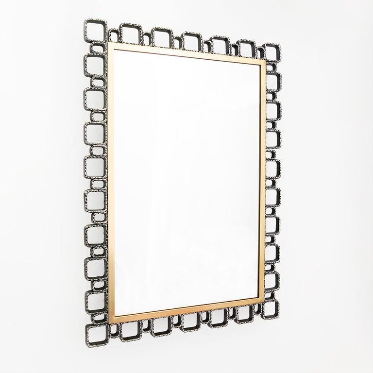 """European Mid-Century Modern wall mirror with built in lights. The mirror's frame is constructed of cast metal elements in the """"Brutalist"""" aesthetic which surrounds a polished and lacquered brass inner frame. Newly restored, cleaned and polished,"""