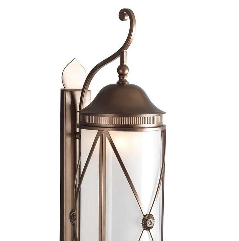 This elegant wall lantern is a striking object of functional decor that will illuminate al fresco dinners on a patio, or flank the entrance door of a house, creating a welcoming and timeless decoration. Its structure is made of forged iron and brass
