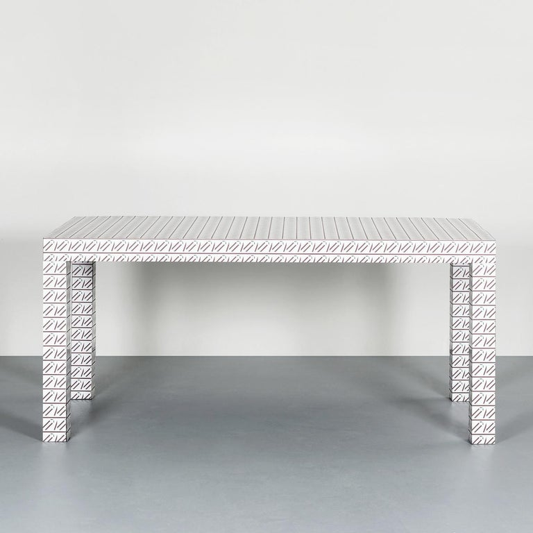 Part of the Hitan collection, this table is a unique addition to an eclectic or contemporary interior, where it can be a stunning dining table or desk. Its Minimalist structure comprises a rectangular top supported by four square cross-section legs.