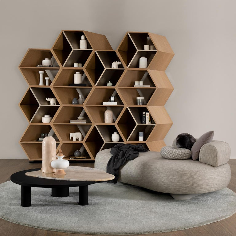 Bookcase with a tridimensional hexagon pattern in open-pore American oak veneer with matt finish. Golden interior shelves lacquered in high-gloss champagne-coloured and satin gold-colored with patina effect bronze powders. Base lacquered in satin