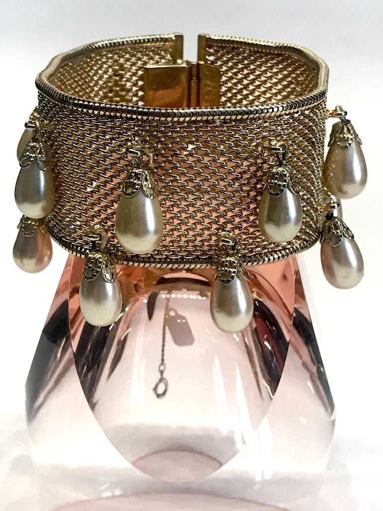 A wonderful vintage Hobe' woven mesh bracelet with pear dangles from the 1950s. The woven band is bordered on both sides with a snake link finish. There are 14 creamy champagne color and pear shape faux pearl bead dangles. Each pearl is set into a