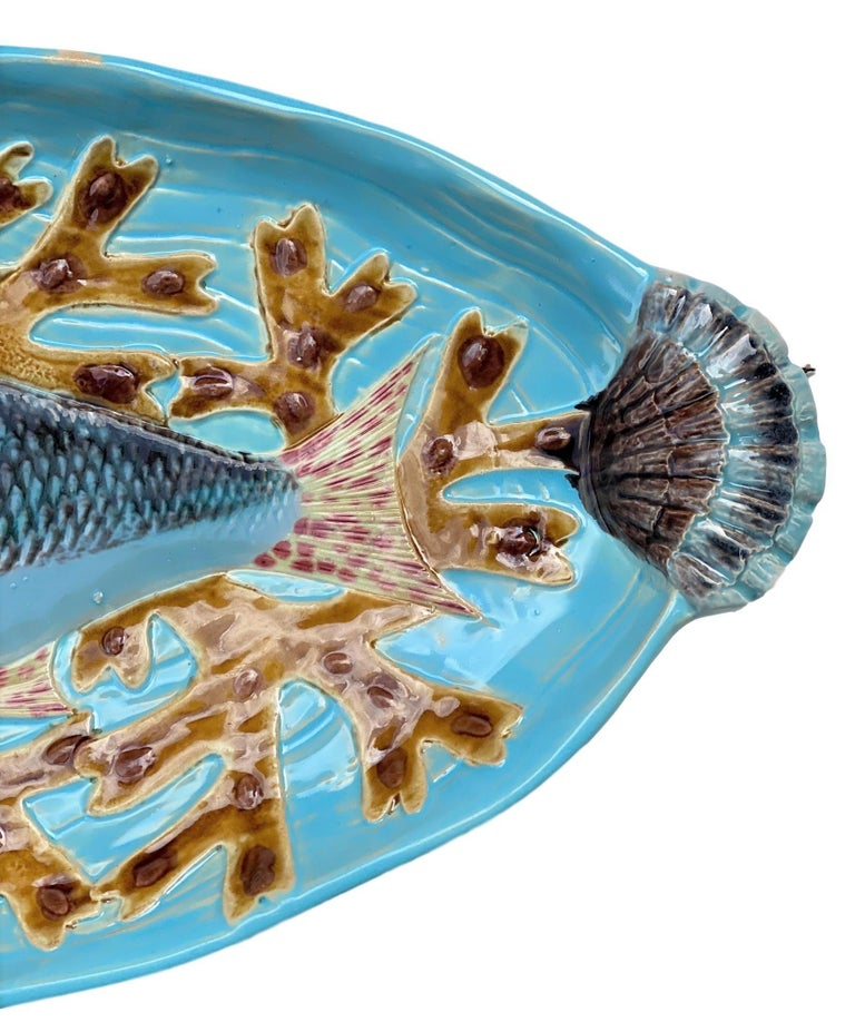 Holdcroft Majolica 7-piece salmon service, English, circa 1875, including a platter, naturalistically molded as a salmon on a bed of seaweeds; on a molded ground simulating moving water, glazed in turquoise blue, with shell form handles molded in
