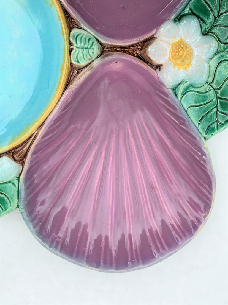 Holdcroft Majolica oyster plate, English, circa 1875, Pond Lily pattern, the wells glazed in deep pink with a hue of lavender.
