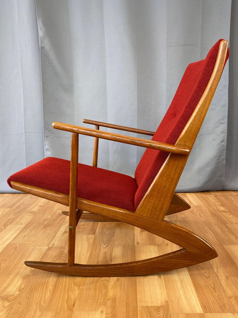 A fantastic Danish modern Model 97 teak rocking chair designed in 1958 by Holger Georg Jensen for Tønder Møbelværk, freshly dressed in vintage red upholstery. Piece pre-dates Jensen's work done for Kubus in the early-to-mid-1960s.  Gorgeous