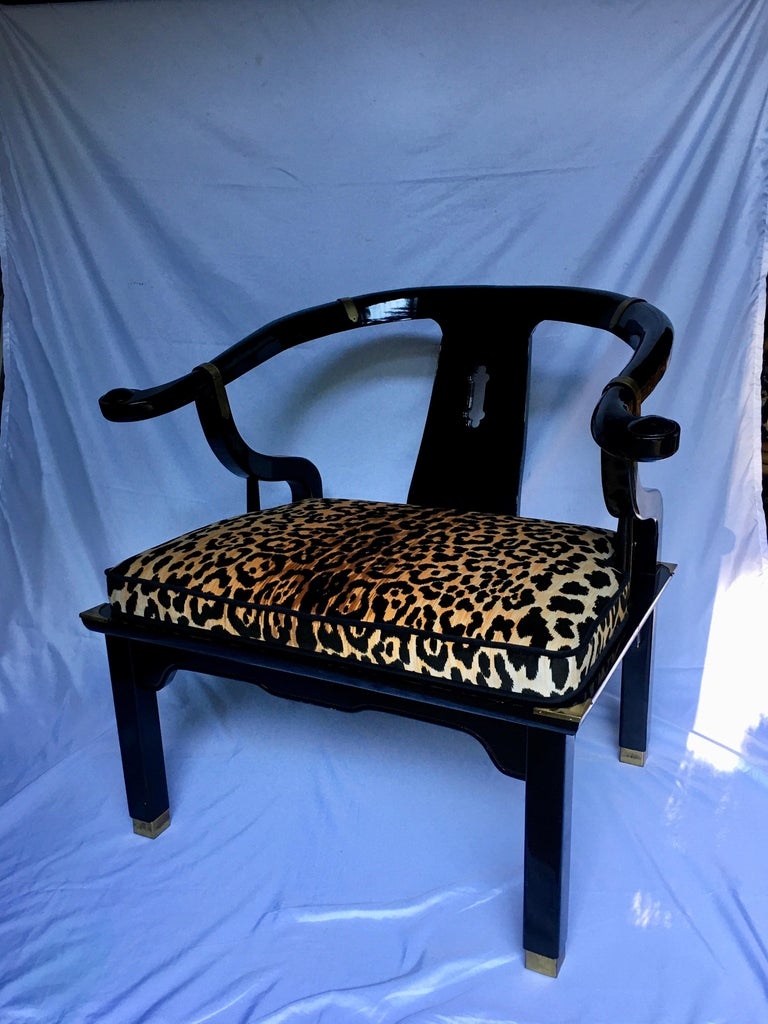 Hollywood Regency style lounge accent chair by Century Furniture. This James Mont style armchair features a gloss black lacquer wood frame with brass hardware accents. Cushion is newly upholstered in a cotton-velvet animal print fabric and piped in