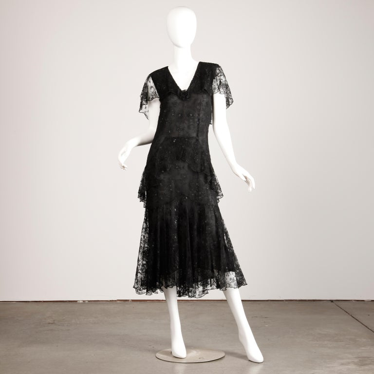 Vintage designer dress by Holly's Harp from the 1980s-90s done in black lace with metallic thread. 1920s Flapper-inspired cut with flutter sleeves and drop waist. Fully lined with single button closure at the back of the neck. There is no marked