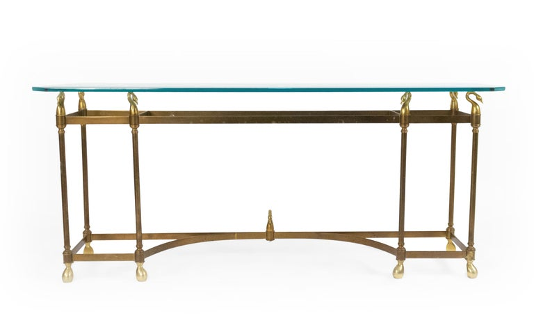 American Mid-20th Century (Hollywood Regency) brass console table with 6 legs and a glass top supported by swan finials with a stretcher base. (attributed to La Barge)