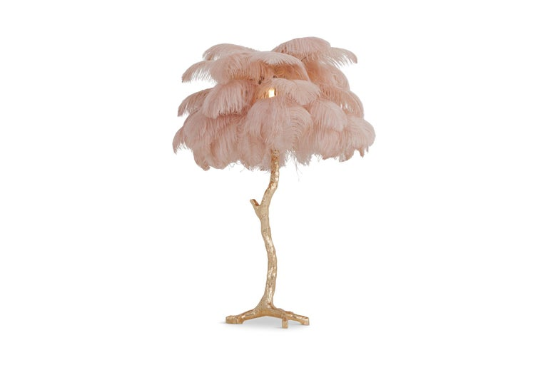 Contemporary lamp with golden resin stem and pink colored ostrich feathers  Decorative luxury piece that fits well in an eclectic Hollywood Regency inspired metropolitan interior  we can also offer the larger floor lamp model.