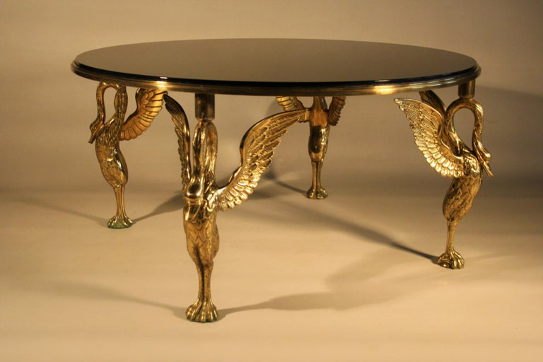 Exceptional Hollywood Regency coffee table made of bronze with a black tinted glass top. The legs of the table represent four swan figures made of solid bronze. A beautiful eye-catcher that fits into any interior.