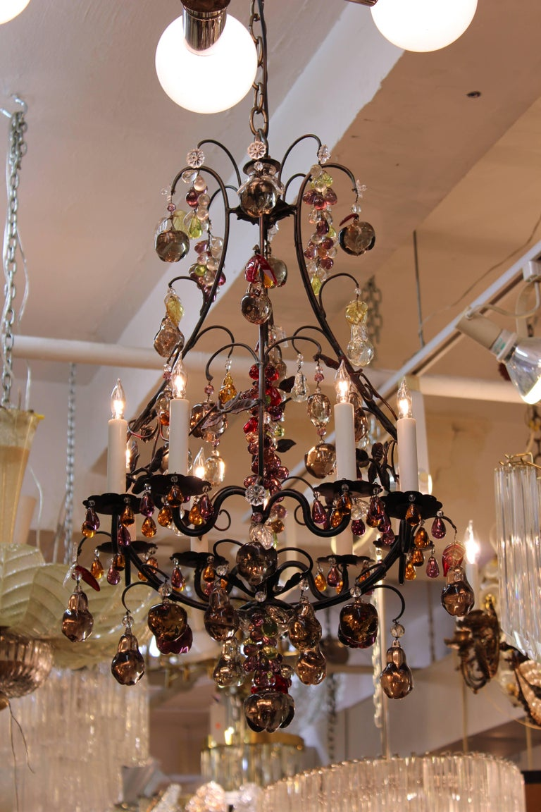 A Hollywood Regency style chandelier with a metal frame and multicolored crystal fruit pendants. The piece is in great condition.