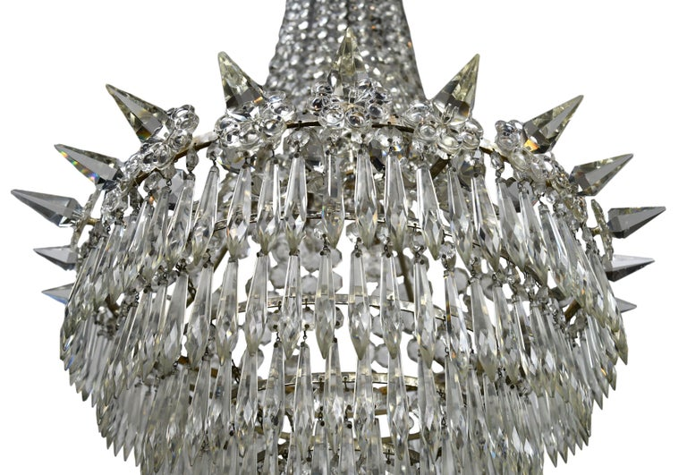 This stunning crystal chandelier features 6 rows of crystals and 24 uniquely shaped spikes adorning the circumference. The copious amount of individual crystals and crystal swag give this chandelier a wonderful golden glimmer when illuminated.