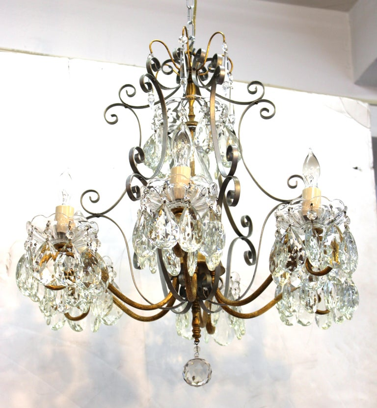 Hollywood Regency crystal chandelier with wrought metal frame and gilt structural accents. The piece takes six candelabra base bulbs and is in great vintage condition.