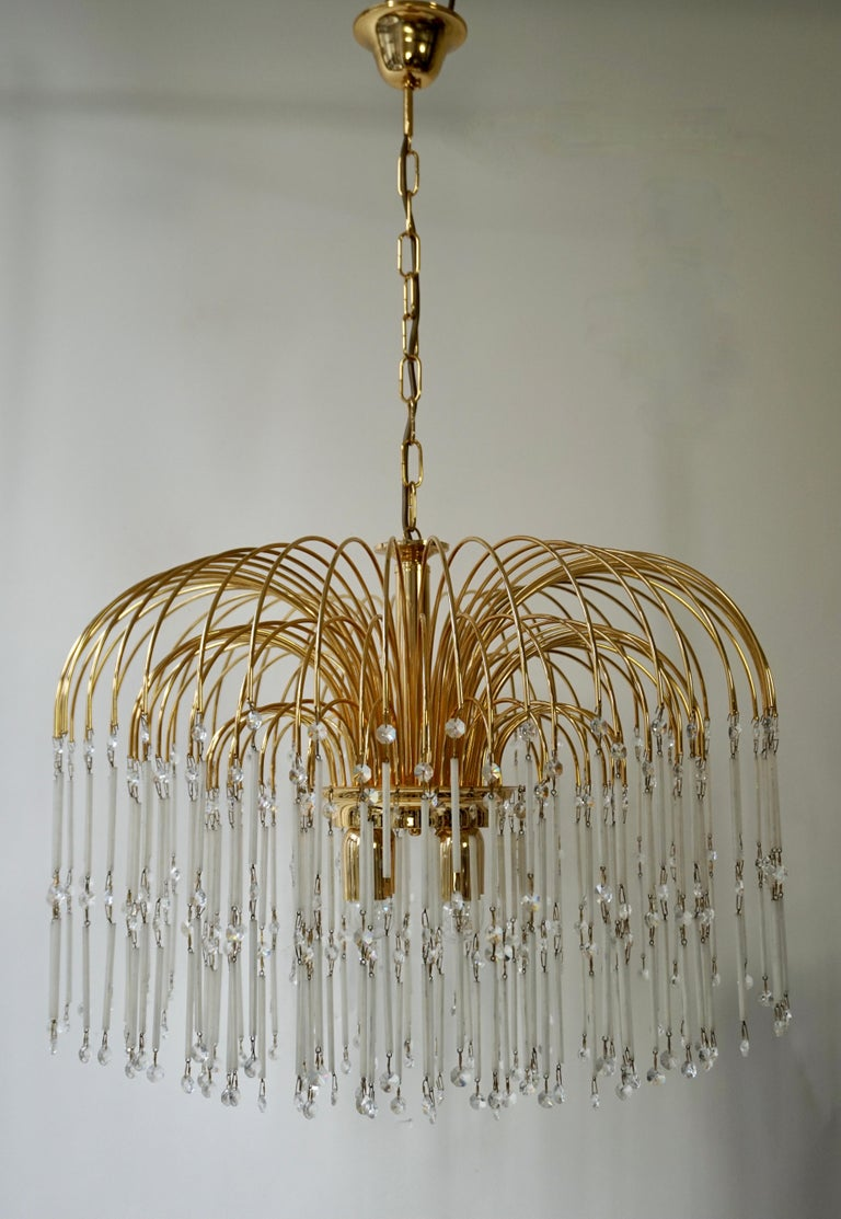 Mid-Century Modern waterfall chandelier with spectacular cut crystals throughout. Features a brass frame with multiple cascading tiers, fitted with of suspended glass tubes and crystal beads. The frame is comprised of three-tier in varying diameters