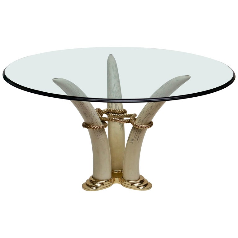 Dining table in gilded bronze and resin in imitation of tusks linked together by a rope. Measures: Diameter glass 140 cm. Height 74 cm. Diameter tusk 80 cm.