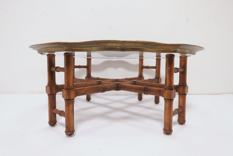 Coffee table in an elegant far East style, faux bamboo trestle form base and a solid brass pie-crust framed glass top. These tables are usually attributed to Baker Furniture Co.