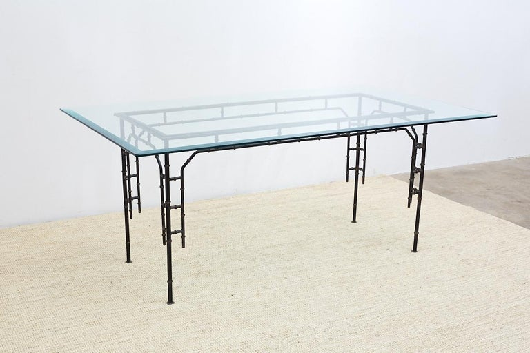 Chic faux bamboo dining or patio table constructed from iron in the Hollywood Regency period. Features an elegant frame with a delicate look but very strong and stabile. Topped with a pane of beveled glass with rounded corners but could support a